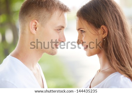Happy girl and her boyfriend looking at one another - stock photo