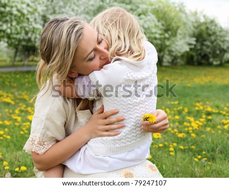 happy girl and her mother in the spring park - stock photo