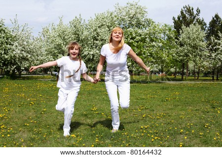 happy girl and her mother in the spring park among flowers