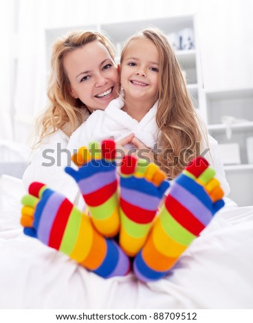 Happy girl and woman at home after bath wearing colorful socks - stock photo