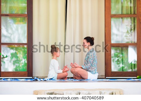 Happy girl annd her mother doing yoga exercise outdoors - stock photo