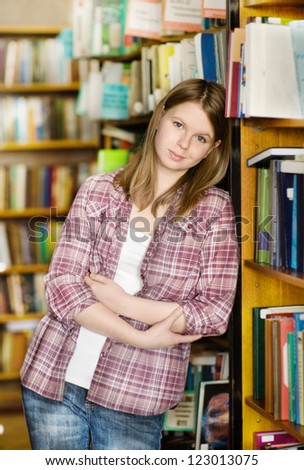 Happy girl at the library. looking at camera - stock photo