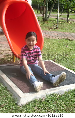 Happy girl at the playground in the park - stock photo