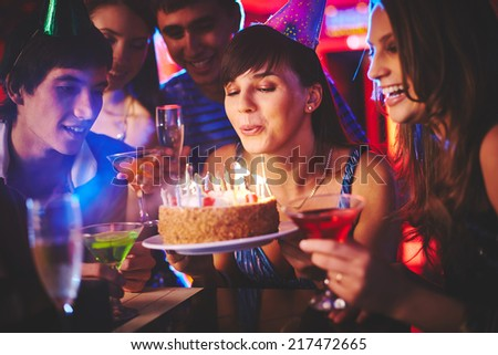 Happy girl blowing on candles on birthday cake with her friends near by