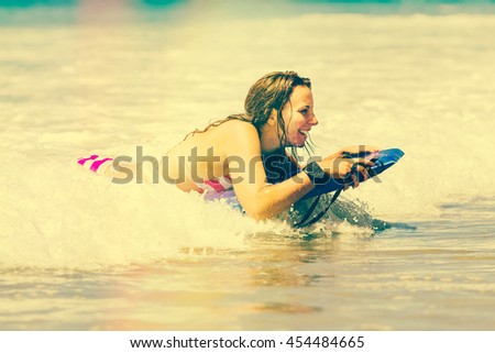 Happy girl boogie boarding at beach - stock photo