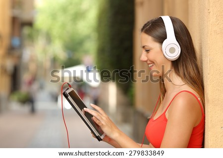 Happy girl browsing a tablet and listening to the music with headphones leaning on a wall in the street - stock photo