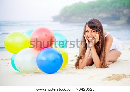 Happy girl  bunch of colorful air balloons at the beach - stock photo