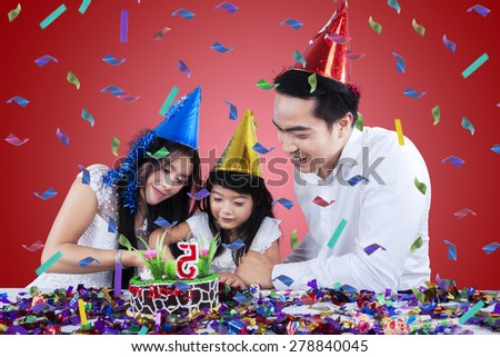 Happy girl celebrate her birthday and cutting birthday cake with her parents - stock photo