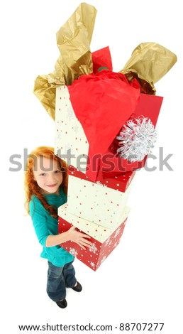 Happy girl child standing over white holding stack of gift boxes smiling.