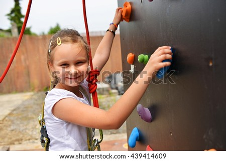 Happy girl climbing wall