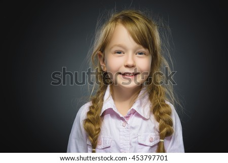 Happy girl. Closeup Portrait handsome child smiling isolated on grey - stock photo