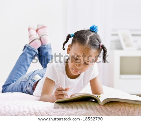 Happy girl coloring in coloring book - stock photo