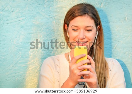 Happy girl connected to social media network and having fun with smartphone. Young woman smiling and typing on the phone against blue wooden background. Lifestyle concept of new trends and technology. - stock photo