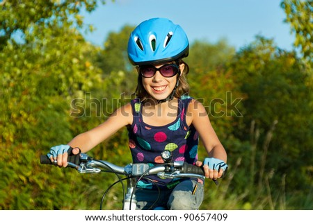 Happy girl cycling outdoors. Smiling child on bicycle