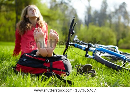 Happy girl cyclist enjoying relaxation sitting barefoot outdoors in spring sunny park