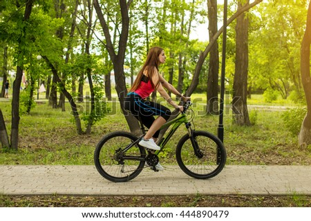 Happy girl cyclist riding on a mountain bike outside on the park. lifestyle sport concept - stock photo