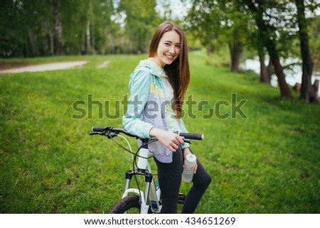 Happy girl cyclist standing with a mountain bike and drinking water. Adventure travel.