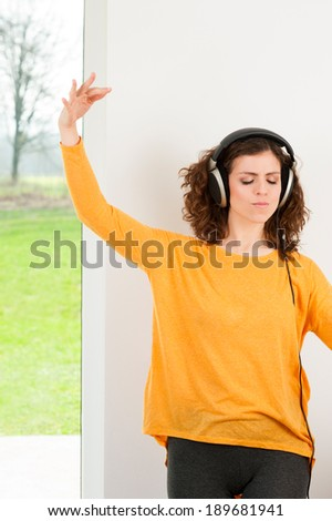 Happy girl dancing at home while listen music with headphones. She is in her house in front of the big window in nature view - stock photo