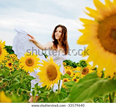 happy girl  dancing in the field of sunflowers - stock photo