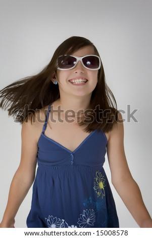 Happy girl dancing, wearing sunglasses - stock photo