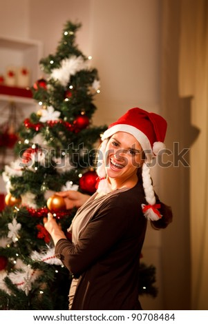Happy girl decorating Christmas tree - stock photo