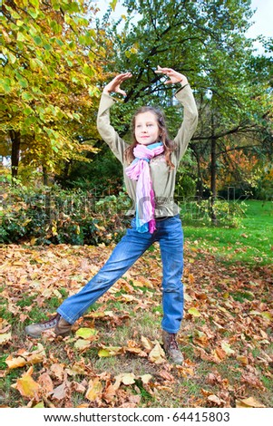 Happy girl do exercise and relaxing outdoors in autumn colored park