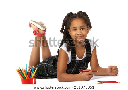 happy girl draws and writes lying on the floor - stock photo