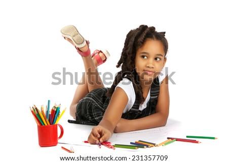 happy girl draws and writes lying on the floor - stock photo