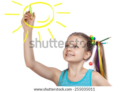 happy girl draws the sun. cheerful girl writes marker on a white background - stock photo
