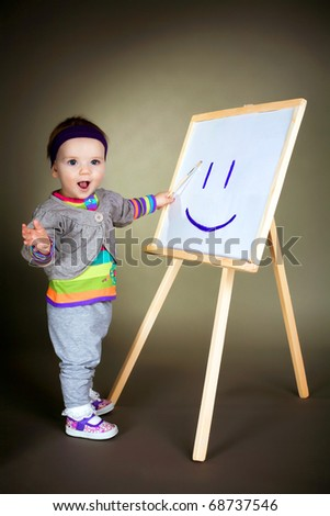 happy girl draws with brush on easel - stock photo