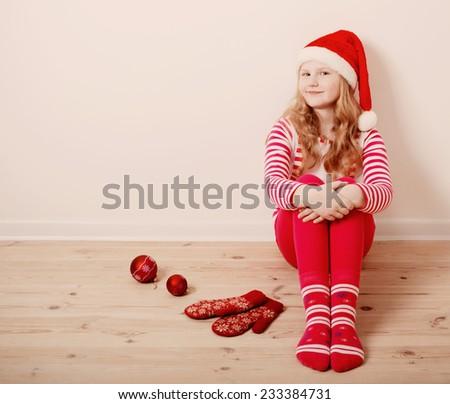 Happy girl dressed in Santa Claus hat - stock photo