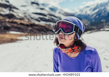 Happy girl dressed in ski or snowboard fashion mask goggles. Mountain landscape. Extreme adventure.  - stock photo