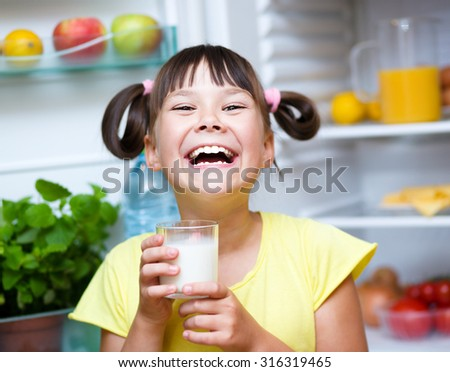 Happy girl drink milk standing near refrigerator with fruits and vegetables - stock photo