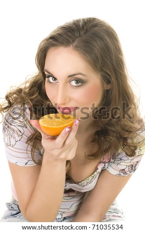 happy girl eating an orange over white background