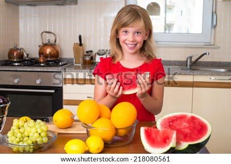 Happy girl eating fruit at a table, concept of health care and healthy child nutrition. Child with organic food or different fruit. - stock photo