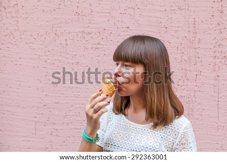 Happy girl eating ice cream on a pink background