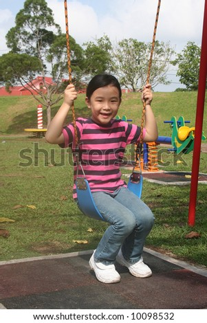 Happy girl enjoy swinging at the playground in the park - stock photo