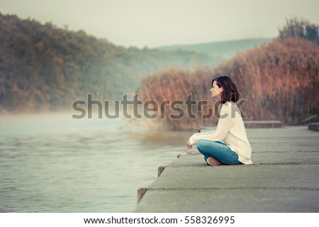 Happy girl enjoys morning by lake. Mist over water. Chilly morning.