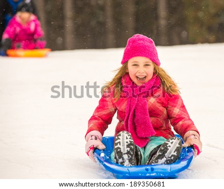 Happy girl expressing joy while sledding in the snow in the winter. - stock photo