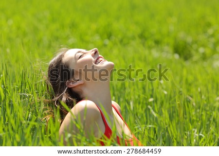 Happy girl face breathing fresh air and enjoying the sun in a meadow in a summer sunny day - stock photo