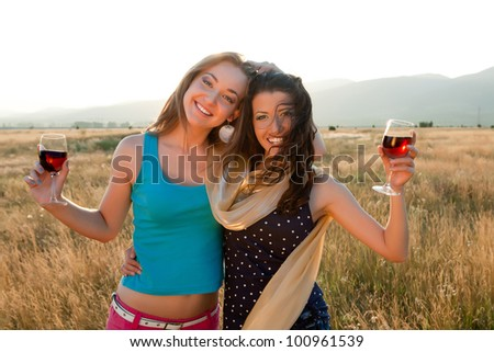 Happy girl friends drinking wine during the golden evening hour - stock photo