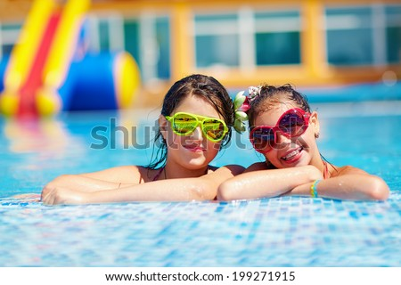 happy girl friends enjoy swimming in the pool - stock photo