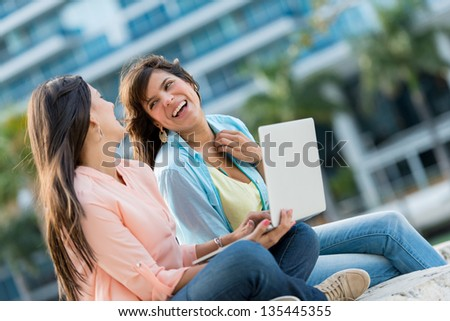 Happy girl friends with a laptop at the park
