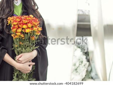 Happy girl graduating holding flowers - stock photo