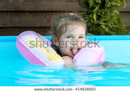 Happy girl having a rest and playing on the swimming pool at the day time, summertime outdoor, friendly family weekend concept.  - stock photo