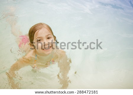 Happy girl having fun in swimming pool - stock photo