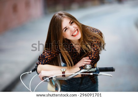 Happy girl having fun, laughing. Having long blonde-brown hair and perfect smile. Staying at the street with bicycle.  - stock photo