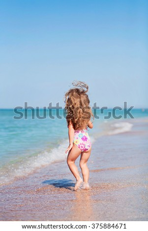 happy girl having fun on a beach, back view