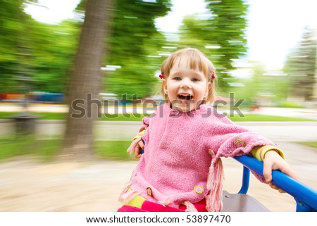 Happy girl having fun on the roundabout - stock photo