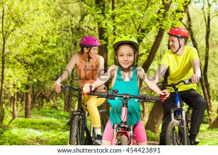 Happy girl having fun the cycling with her parents